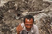 Yoyok (55 years old) is a tin miner since 2000. Illegal tin mine in Reboh. Bangka Island (Indonesia) is devastated by illegal tin mines. The demand for tin has increased due to its use in smart phones and tablets.  Illegal tin mining causes environmental damage, injuries and regular casualties (100-150 persons die every year).   <br /> <br /> Yoyok (55 ans) cherche de l'étain depuis 2000.  Mine d'étain illégale à Reboh. L'île de Bangka (Indonésie) est dévastée par des mines d'étain sauvages. La demande de l'étain a explosé à cause de son utilisation dans les smartphones et tablettes. Les Mines illégales son la cause des dommages écologiques, des blessés graves et décès (100 - 150 tous les ans)....