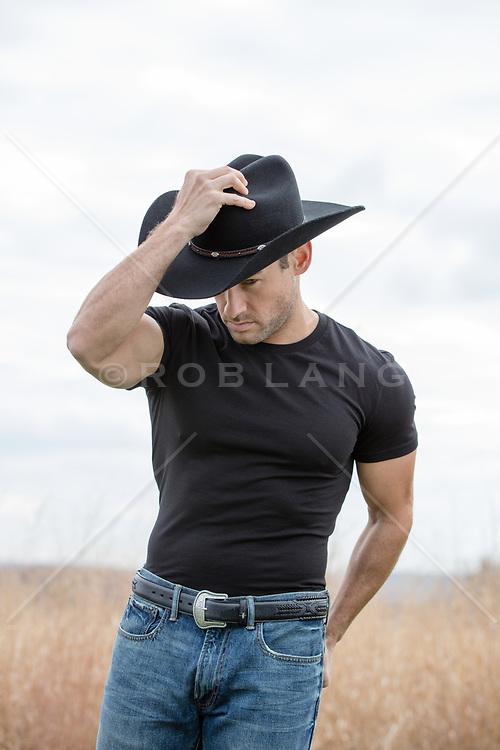 muscular cowboy in a black tee shirt outdoors