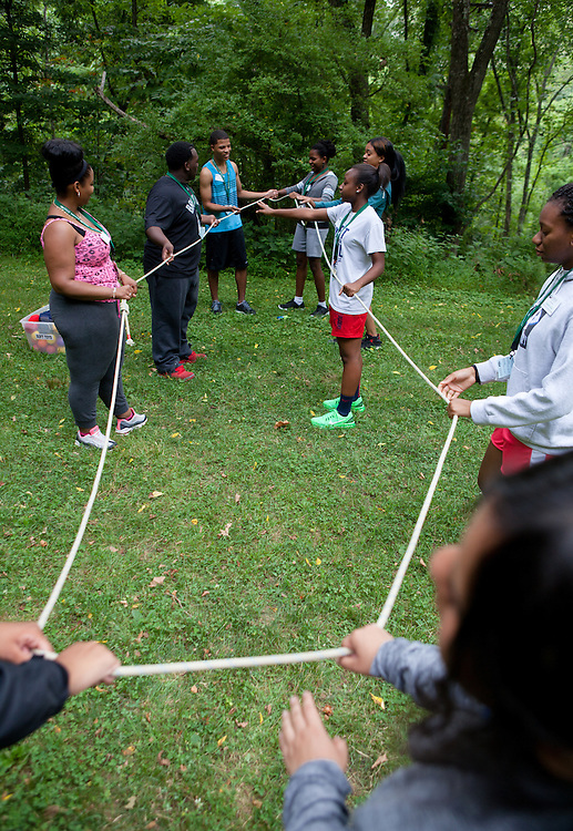 Participants in Ohio University's Junior Executive Business Program close their eyes and collaborate  to form polygons with a rope during the Ropes Challenge Course on July 13, 2014. Photo by Lauren Pond