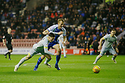 Derby County midfielder Harry Wilson (7) goes down under a challenge from Wigan Athletic defender Dan Burn (33)  during the EFL Sky Bet Championship match between Wigan Athletic and Derby County at the DW Stadium, Wigan, England on 8 December 2018.