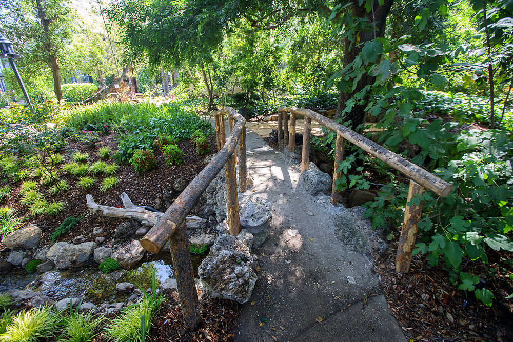 The stone bridge and rustic timber railing crossing over the Stream and Pond by Mystic Water Gardens -after renovations outside the Pasadena Showcase House of Design on Wednesday, April 12, 2017 in Pasadena, Calif. The 1916 English estate home was updated for modern living by interior and landscape designers. © 2017 Patrick T. Fallon