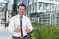 Portrait of confident businessman showing thumbs up outside office building