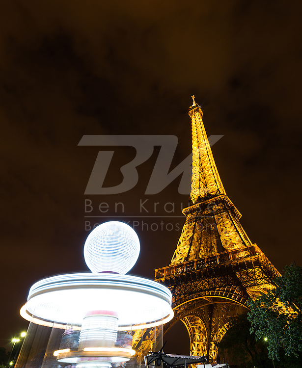 A merry-go-round spins near the Eiffel Tower in Paris, France on May 18, 2012.