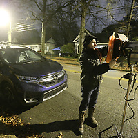 Michael Williams installs a colored gel to a light before the crew starts filimg on North Green Street Monday night.