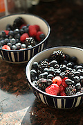 Two bowls of summer berries -- including raspberries, blackberries and blueberries -- on a granite countertop.