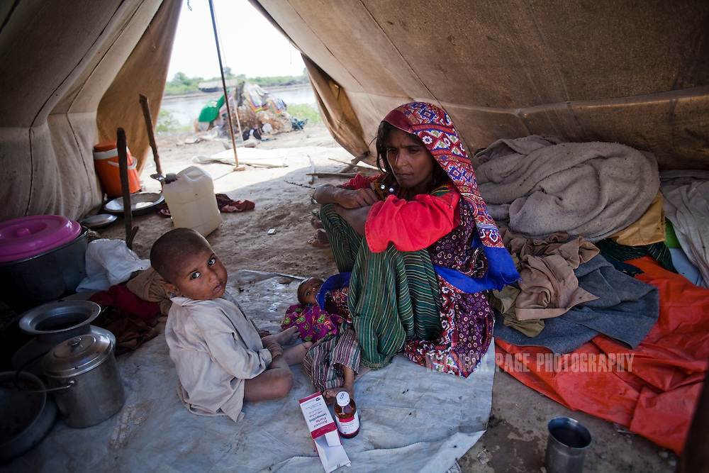 Banno, 30, sits in her tent with baby Ameena, 8 months, and other children, on October 15, 2011, in Pangrio, Pakistan. Banno has been suffering from TB for the last 12 months, while Ameena became malnourished 1 months before the floods began and became progressively worse after they were forced to flee their home. Extreme poverty, poor diet and health, exposure to disease, and inadequate sanitation and hygiene annually produce alarming levels of malnutrition amongst children, but the floods of 2010 and 2011 have increasingly endangered an already vulnerable population. Child malnutrition has breached emergency levels in Pakistan - particularly Sindh province - after monsoon floods devastated the country's poorest region for a second year. Malnourishment It is the single biggest contributor to under-five mortality, increasing the risk of infections and slowing recovery from illness. It stuns both mental and physical growth and their future capacity, sapping the next generation's ability to meet the demands of a country already facing an unstable future. According to UN reports, hundreds of thousands of children in Pakistan suffer from severe-acute-malnutrition, with 15.1% of children experiencing acute malnourishment. The Economist recently reported that 44% of children in Pakistan suffer from varying degrees of malnutrition. (Photo by Warrick Page)