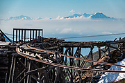 Chugach Mountains rise beyond a collapsing railway at Independence Mine State Historic Park, 14 miles from Palmer, Alaska, USA. The Independence Mines were a gold mining operation in the Talkeetna Mountains, across Hatcher Pass from Palmer. Independence Mine was the second-largest hard-rock gold mining operation in Alaska, after a larger site near Juneau. Mining here dates back to 1897 around Fishook Creek; these claims joined to form Wasilla Mining Company, which worked the mines from 1934-1943 and again 1948-1950. The company ended operations in 1950 expecting to resume, but never did, thereby well-preserving its mining equipment and buildings for eventual donation to the state in 1980, which established Independence Mine State Historic Park.
