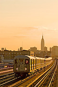 New York City. The Number 7 elevated subway Near 46th Street in Queens with the Empire State Building in the background.