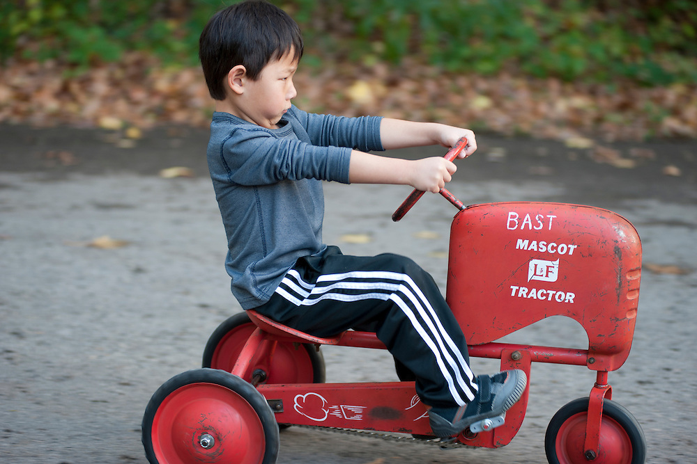 Holden Miller, 4, rides his vintage-toy pedal tractor on the along the street in front of the Miller/Stute home in Madison, Wis., during autumn on Oct. 24, 2011.
