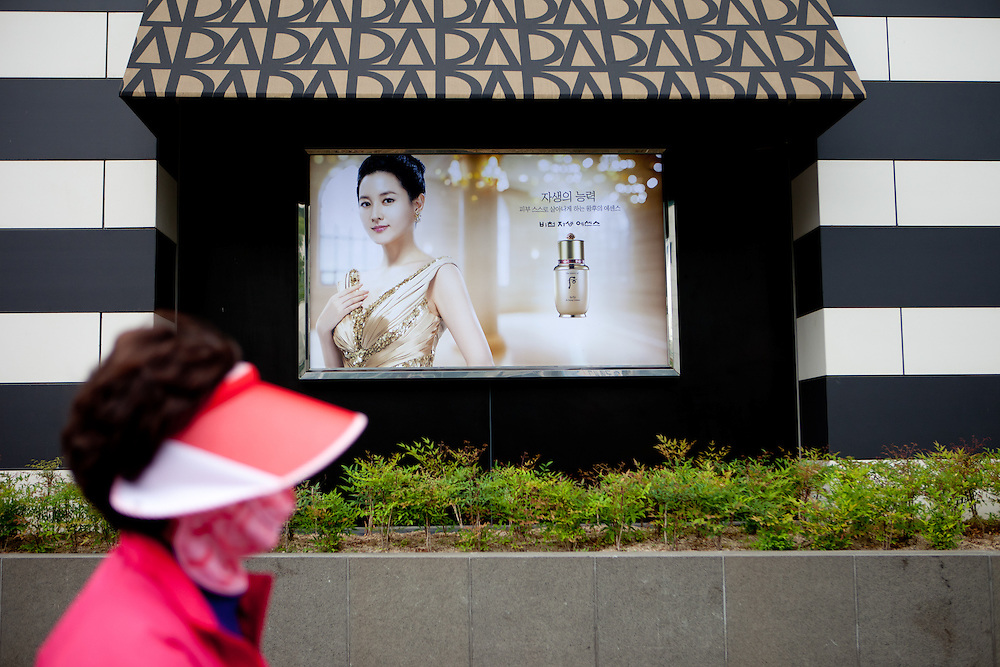 A woman with mouth protection passing a commercial in the city of Daegu.