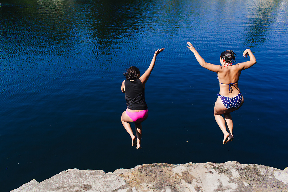 Young woman jumping into quarry