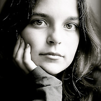 Young girl with long dark hair looking confidently at camera with head resting on hand