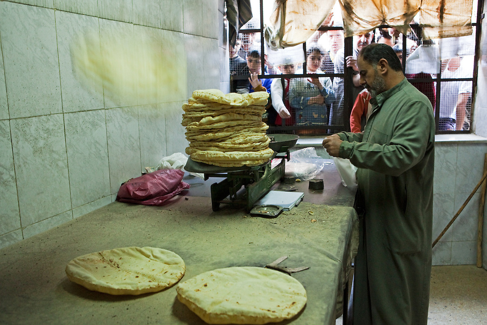 Flatbread falls from a conveyor belt onto a weighing table before being sold, to the waiting public, Aleppo, Syria