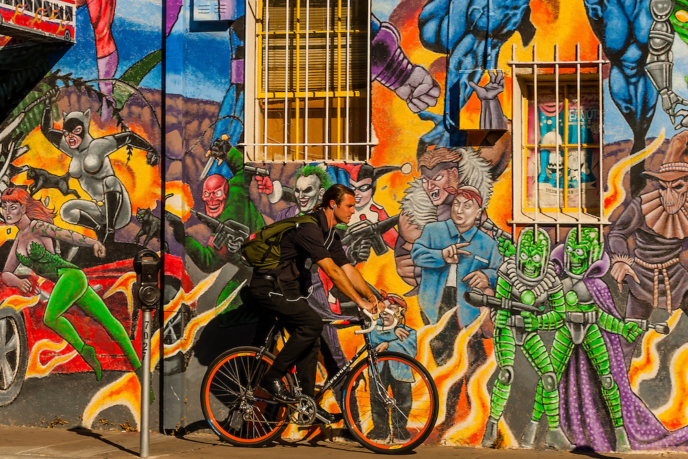 """An urban bicyclist riding down the sidewalk with a mural of comic book super heroes on the side of """"Masks Y Mas"""" store in background, Albuquerque, New Mexico USA"""