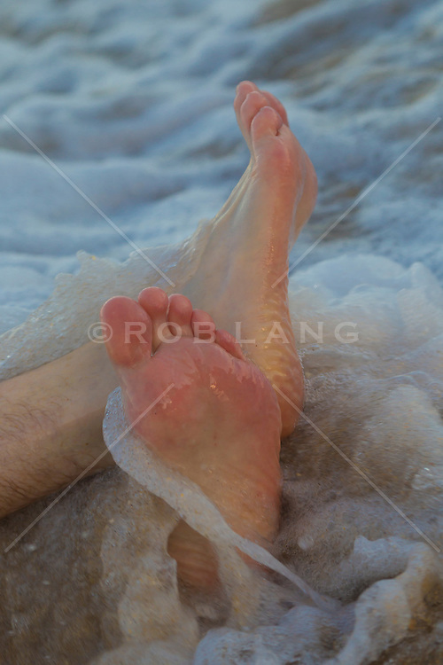 man's feet in the ocean