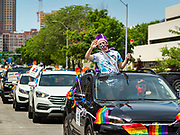 "28 JUNE 2020 - DES MOINES, IOWA: The ""Queen"" of the Capitol City Pride Parade is driven up Grand Avenue in Des Moines during the parade. Most of the Pride Month events in Des Moines were cancelled this year because of the COVID-19 pandemic, but members of the Des Moines LGBTQI community, and Capitol City Pride, the organization that coordinates Pride Month events, organized a community ""parade"" of people driving through the East Village of Des Moines displaying gay pride banners and flags. About 75 cars participated in the parade.     PHOTO BY JACK KURTZ"
