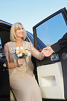 Man helping middle-aged woman from limousine