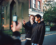 Kevin and Chris being photographed on mobile, UK, 2000s.