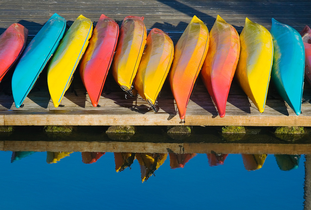 Colorful sea kayaks lined up on a dock.