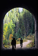 Bicylists exiting train tunnel along the Hiawatha Rails to Trails project. Benewah County in the Bitterroot Mountains, Idaho.
