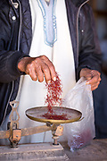 ASSAISS, MOROCCO - October 28th 2015 - A trader weighs saffron stigmas for a customer at the Assaiss market, Taliouine, Morocco