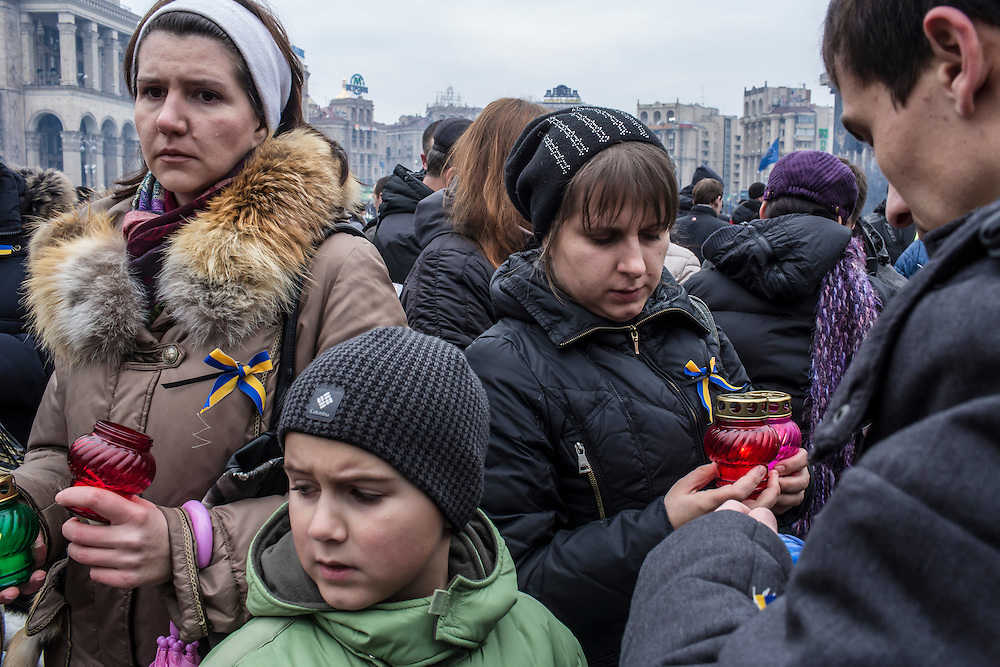 KIEV, UKRAINE - FEBRUARY 23: People prepare to place candles at a memorial to anti-government protesters killed in chashes with police on Independence Square on February 23, 2014 in Kiev, Ukraine. After a chaotic and violent week, Viktor Yanukovych has been ousted as President as the Ukrainian parliament moves forward with scheduling new elections and establishing a caretaker government. (Photo by Brendan Hoffman/Getty Images)