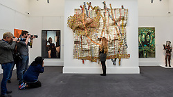 "© Licensed to London News Pictures. 12/05/2017. London, UK.   Members of the media photograph a staff member viewing ""Earth Developing More Roots"", 2011, by El Anatsui (Ghana) (Est. GBP 650-850k) at the preview for the first sale dedicated to Modern and Contemporary African Art at Sotheby's New Bond Street.  The sale features over 115 artworks by over 60 different artists from 14 countries across the continent. Photo credit : Stephen Chung/LNP"