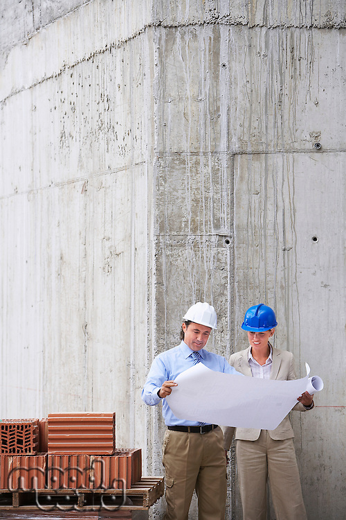 Construction manager and architect examining plans on site