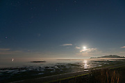 A full moon and the stars at Dungeness Landing during low tide, Sequim WA. Dungeness Lighthouse lights up the tip of the Spit in the distance.