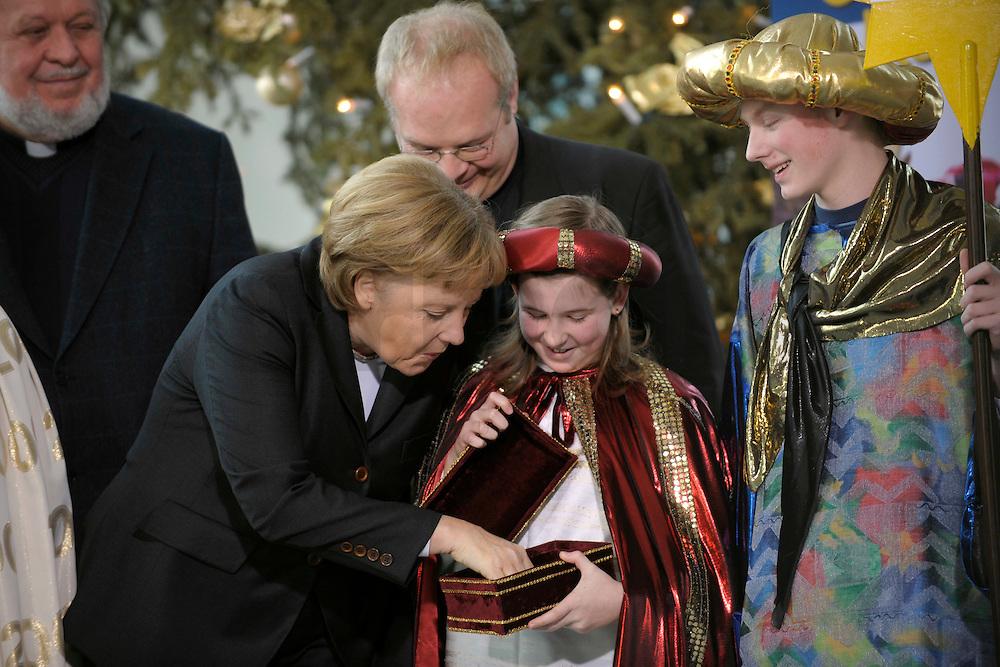 04 JUN 2008, BERLIN/GERMANY:<br /> Angela Merkel, CDU, Bundeskanzlerin, schaut einem der Heiligen drei Koenige in die Goldtruhe, waehrend dem Empfang der Sternsinger im Bundeskanzleramt<br /> IMAGE: 20080104-01-013<br /> KEYWORDS: Heilige drei Koenige, Heilige drei Könige, Kanzleramt