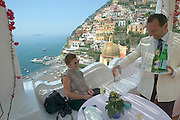 View over the town and the Amalfi Coast. Nicole Schmidt having a drink at Hotel La Sirenuse.