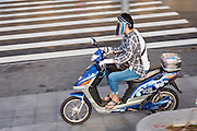 A chinese woman rides an electric scooter wearing a face mask in Shanghai, China