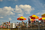 Brooklyn, New York, USA. 10th August 2013. Seen from below, outside Nathan's Famous boardwalk restaurant, the picnic tables, with colorful red yellow and green umbrellas, are filled with people eating during the 3rd Annual Coney Island History Day celebration. At left, a man chains his bicycle to the boardwalk railing.