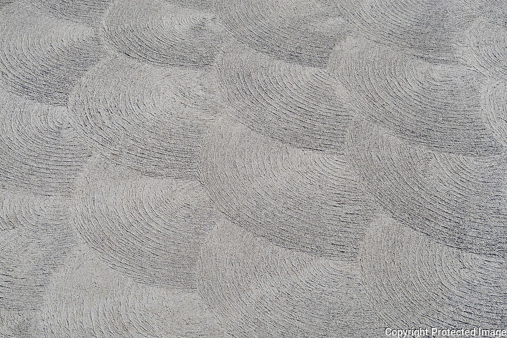 Abstract of swirling patterns in cement sidewalk