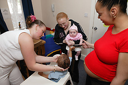 Pregnant young woman with her friends and their babies,