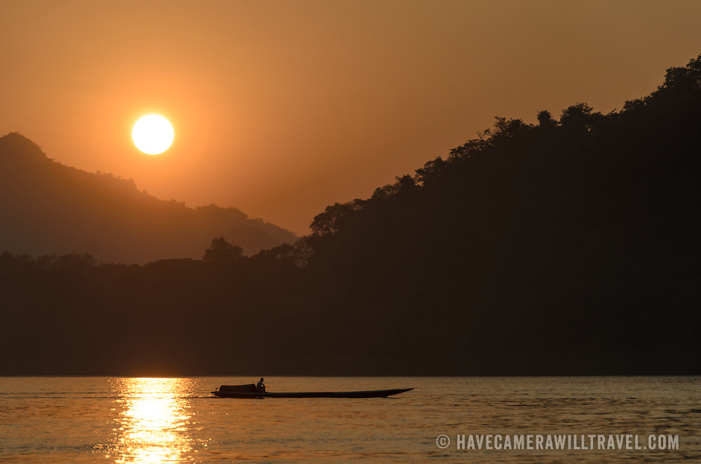 A motorized sampan crosses the river just before the sun goes down behind the moutnains on the Mekong River near Luang Prabang, Laos.