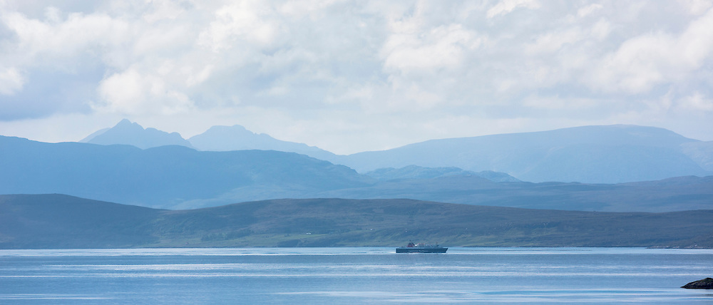 Caledonian Macbrayne ferry (Calmac) passes The Summer Isles and in distance Isle of Skye, part of the Inner Hebrides, on route to the Outer Hebrides on the West Coast of Scotland
