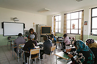 "SUTERA, ITALY - 8 JANUARY 2018: Asylum seekers attend afternoon Italian classes for adults in the elementary school of Sutera, Italy, on January 8th 2018.<br /> <br /> Sutera is an ancient town plastered onto the side of an enormous monolithic rock, topped with a convent, in the middle of the western half of Sicily, about 90 minutes by car south of the Sicilian capital Palermo<br /> Its population fell from 5,000 in 1970 to 1,500 today. In the past 3 years its population has surged  after the local mayor agreed to take in some of the thousands of migrants that have made the dangerous journey from Africa to the Sicily.<br /> <br /> ""Sutera was disappearing,"" says mayor Giuseppe Grizzanti. ""Italians, bound for Germany or England, packed up and left their homes empty. The deaths of inhabitants greatly outnumbered births. Now, thanks to the refugees, we have a chance to revive the city.""<br />  Through an Italian state-funded project called SPRAR (Protection System for Refugees and Asylum Seekers), which in turn is co-funded by the European Union's Fund for the Integration of non-EU Immigrants, Sutera was given financial and resettlement assistance that was co-ordinated by a local non-profit organization called Girasoli (Sunflowers). Girasoli organizes everything from housing and medical care to Italian lessons and psychological counselling for the new settlers.<br /> The school appears to have been the biggest beneficiary of the refugees' arrival, which was kept open thanks to the migrants.<br /> Nunzio Vittarello, the coordinator of the E.U. project working for the NGO ""I Girasoli"" says that there are 50 families in Sutera at the moment."