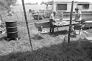 A couple preparing food outside in a small garden, at Glastonbury, 1989