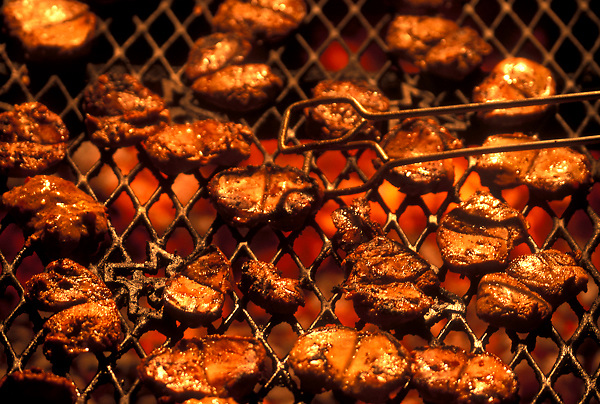 Stock photo of small cuts of meat grilling on an outdoor grill