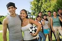 Young couple with woman holding soccer ball group of friends in background.