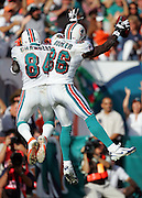 MIAMI - DECEMBER 10:  Wide receiver Marty Booker #86 of the Miami Dolphins jumps in celebration and does a hip bump with teammate Chris Chambers #84 after Booker catches a touchdown pass for a 13-0 lead against the New England Patriots at Dolphin Stadium on December 10, 2006 in Miami, Florida. The Dolphins defeated the Patriots 21-0. ©Paul Anthony Spinelli *** Local Caption *** Marty Booker;Chris Chambers