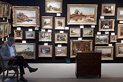 © licensed to London News Pictures. LONDON, UK  08/06/2011. An art dealers takes a break at the Olympia International Fine Art & Antiques Fair. All 30,000 items on sale from 150 dealers are vetted for authenticity by a panel of experts. The show opens in Olympia tomorrow (Thursday) and runs for 11 days. Please see special instructions for usage rates. Photo credit should read CLIFF HIDE/LNP
