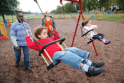 Man and woman pushing boy and girl on a swing