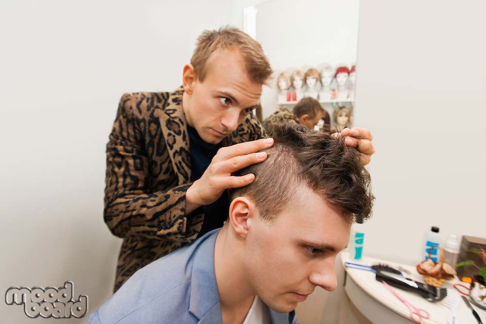Professional barber examining male customer's in shop