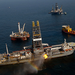 The drill ship Discoverer Enterprise creates a rainbow effect as water is sprayed near where gas brought up from the cap placed over the damaged well burns off, also some oil is reportedly being pumped up to the ship from the damaged well head in the Gulf of Mexico near the coast of Louisiana, U.S., on Saturday, June 5, 2010. The biggest oil spill in U.S. history, which began when BP Plc's Deepwater Horizon rig exploded on April 20, has soiled about 140 miles (225 kilometers) of coastline, halted new exploratory deep-water drilling in the Gulf and shut down a third of its fishing areas. Photographer: Derick E. Hingle/Bloomberg