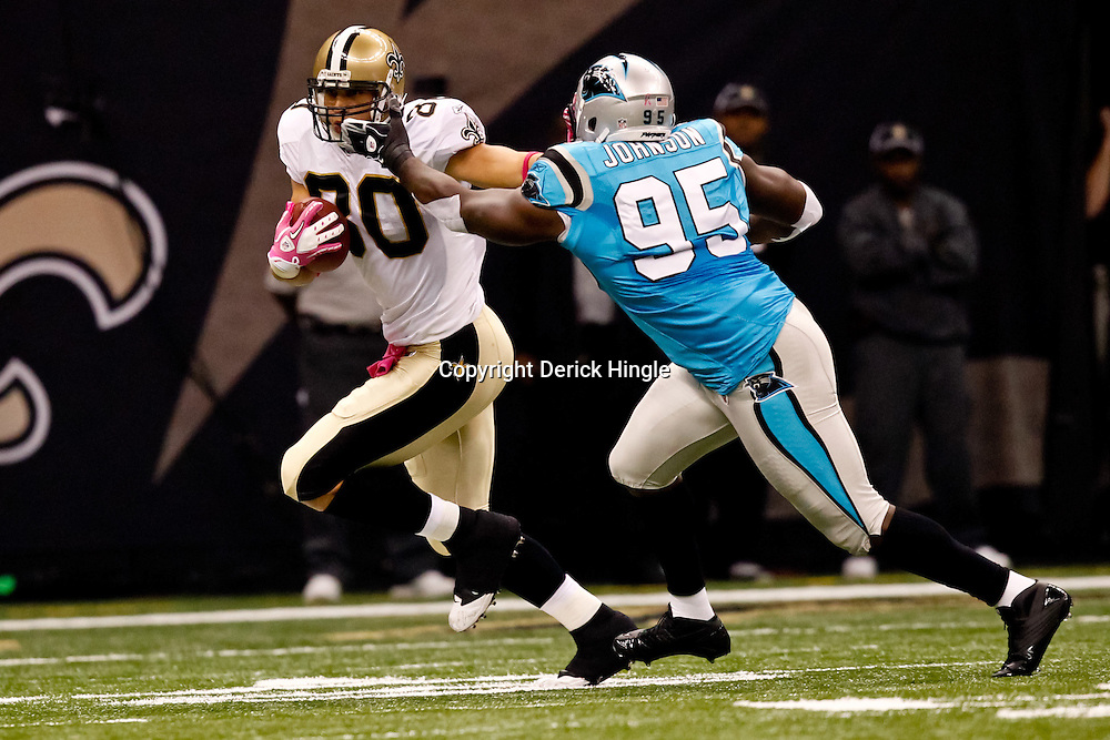 October 3, 2010; New Orleans, LA, USA; New Orleans Saints tight end Jimmy Graham (80) stiff arms Carolina Panthers defensive end Charles Johnson (95) during the first quarter at the Louisiana Superdome. Mandatory Credit: Derick E. Hingle