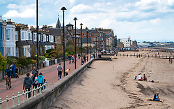 Portobello, Scotland, UK. 9 May 2020. Images from holiday weekend Saturday afternoon during Covid-19 lockdown on promenade at Portobello. Promenade and beach were relatively quiet with a low key police presence. Pictured; View along beach and promenade showing social distancing of people. Iain Masterton/Alamy Live News