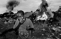 A boy shoves a handful of sugar in his mouth that he found inside an half eaten us military ready o eat meal after fighting others for it in the dump.