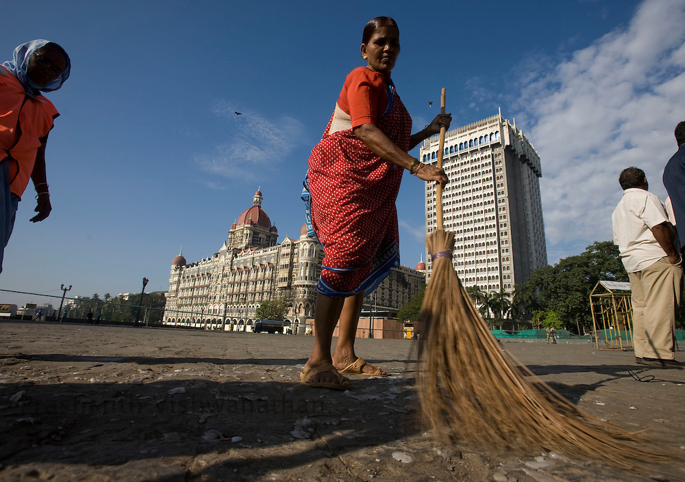 A woman sweeps in fron of the Taj hotel in Mumbai, on Tuesday, Dec. 2, 2008.  The 60-hour killing spree by less than a dozen terrorists in   Mumbai last week underscores the failure of India's police force to keep pace with better armed, equipped and trained militants, a former intelligence agent said.